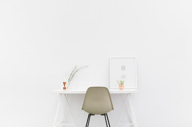 how to live simply. a simple chair and desk with stark, white walls. living with less.