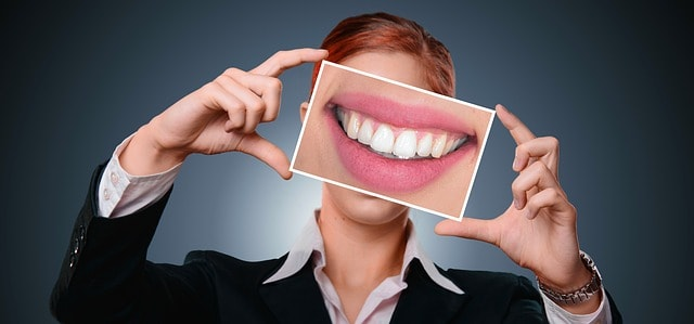 Invisalign review woman smiling after dental work has straightened teeth.