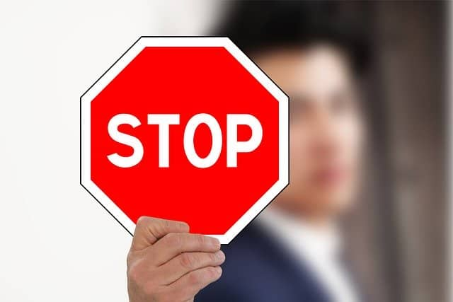 stop buying stuff. man holding up a stop sign